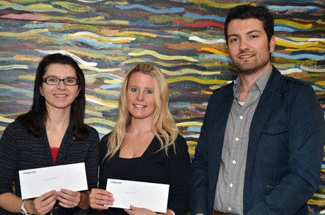 First-year student Lauren Marshall and third-year student Adina Clark are given their travel vouchers by Research Analyst Drew Pihlainen, who helped administer the New to UBC survey.