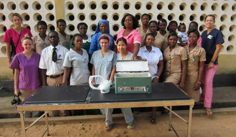 Nursing students present rural African nurses with an examining table and health care equipment purchased with funds raised at the 2011 Global Gala.