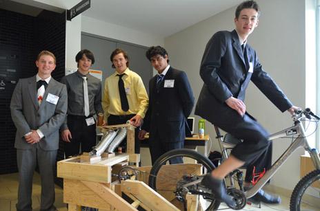 From left: students Matthew Hoffman, Elliot Stewart, Lucas Kocher, Shrayan Joshua Rodricks, and Robert Leigh show off their pedal-powered can crusher.