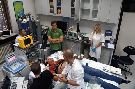 Experiment on a test subject at the University of Split, Croatia. UBC's Anthony Bains, left, and Chris Willie, second from left, monitor readings. Prof. Philip Ainslie, (white shirt, rear) monitors another piece of equipment while Split staff assist.