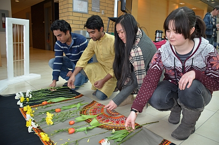 Kader Mewaj, Ashish Dey, Jinglei You and Erika Ablen lay flowers at a memorial to those who died in the 1971 Bangladesh Liberation War that saw the country partitioned and the creation of Bangladesh.