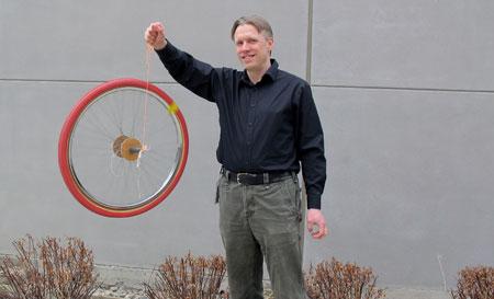 Physics instructor John Hopkinson demonstrates Angular Momentum.