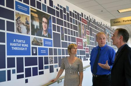 Margo Yacheshyn, Bud Mortenson and Robert Eggleston discuss Our Stories, the new UBC mural at Kelowna International Airport.