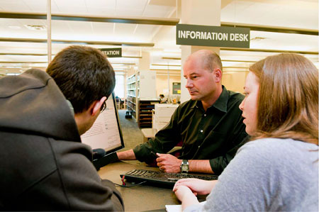 Robert Janke, new deputy chief librarian at UBC's Okanagan Library, helps out students at the information desk.