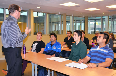 Management professor John Burton recently moved students Mark Brandle, Samin Mahmood, Michael Flaherty-Specht and David Rogas to the front row of his classroom as part of the rolling seats initiative.