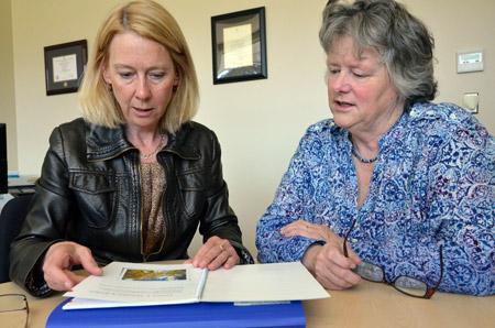 UBC Okanagan Canada Research Chair Barb Pesut and Health Navigator Brenda Hooper look over a workbook created to help train volunteer health navigators to work with chronically ill seniors living in rural communities.