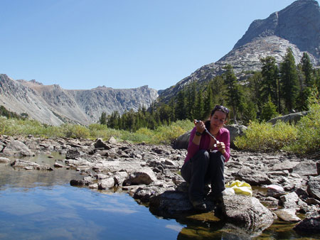 Post-doctoral researcher Janice Brahney takes a water sample at the outlet of Black Joe Lake, Wind River Range, Wyoming to test for phosphorus pollution.