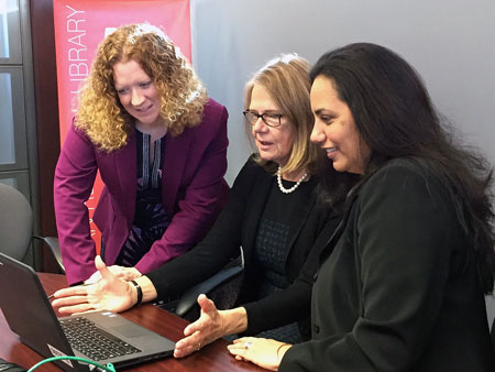 UBC Okanagan chief librarian Heather Berringer, DVC Deborah Buszard, and Pilar Portela, with Accelerate Okanagan, search digital records at the opening of the UBC Innovative Library inside the Kelowna library.