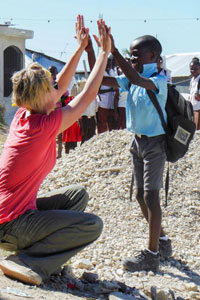 Human Kinetics student Paige Marzinzik high fives a young boy during her last visit to Haiti.