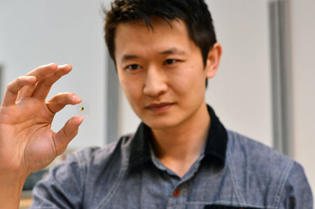 Kenneth Chau holds a glass sample used in his latest research, which proved that putting thin layers of metal over glass increases light transmission.