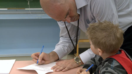 John-Tyler Binfet works with a student at a local elementary school.