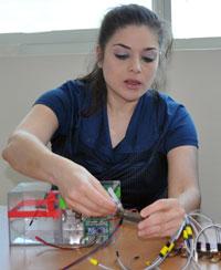 Professor Mina Hoorfar demonstrates the breath tube for the microfluidic breath analyzer.
