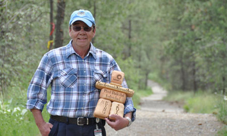 Allan King, former manager of maintenance and grounds, with the City of Kelowna's Most Environmentally Dedicated Individual award he won in 2010. Behind him is the campus trail system, one of the many campus sustainability initiatives King championed over the years.