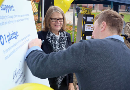 Deputy Vice-Chancellor and Principal Deborah Buszard (left) invites UBC Students' Union Okanagan President Blake Edwards to sign the Okanagan Charter. Following this photo, the Deputy Vice-Chancellor invited all those in attendance to sign the Charter as well.