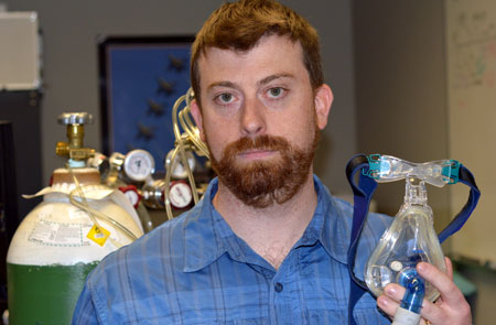Assistant Professor of Health and Exercise Science Glen Foster, seen holding breathing apparatus in his lab, is researching the health impacts of sleep apnea.
