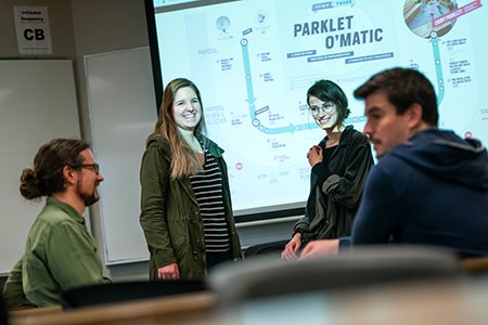 Cultural Studies students Tessa Baatz and Emma Mcleod (centre) present their project in class.
