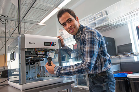 Hossein Montazerian, research assistant with the School of Engineering, demonstrates the artificial bone design that can be made with a 3D printer.