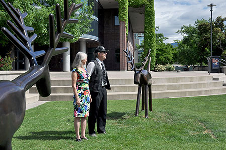 """Louise Sidley, left, and David Sidley speak to family and friends gathered after the sculpture """"Pair of Deer"""" was officially unveiled at UBC's Okanagan campus."""