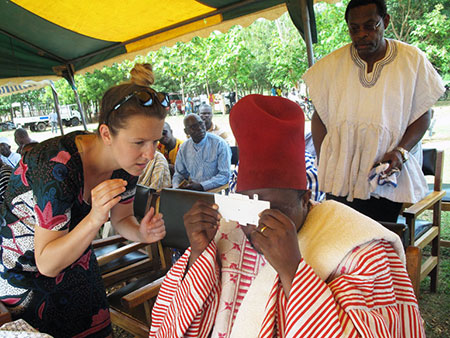 Faculty of Education's Carly Bokor shows Paramount Chief of the Nabdam Region how to use the Foldscope.