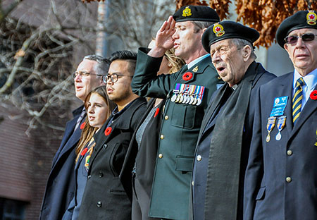 Lieutenant-Colonel Mike McGinty, centre, salutes at UBC Okanagan's 2016 Remembrance Day service.
