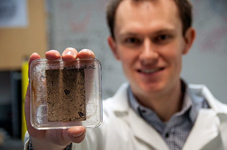 School of Engineering researcher Bryn Crawford holds a sample sheet made with flax bio-waste. The black spots on the sheet indicate mould growth.