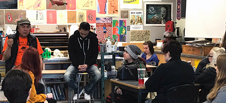 Activist Dixon Terbasket (front left) and artist Sheldon Louis (front right) speak to Kelowna Secondary School students about the impact of colonialism on Syilx culture.
