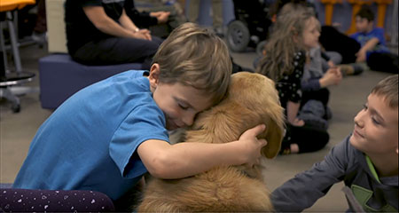 A picture of a young boy hugging a golden retriever