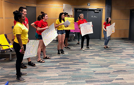 Peer Leaders and Senior Peer Leaders form a greeting squad at the airport.