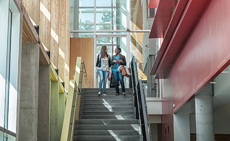 A picture of two staff members walking down a set of stairs