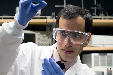 UBC doctoral student Hossein Montazerian takes a close look at a tiny sensor embedded into a fibre.
