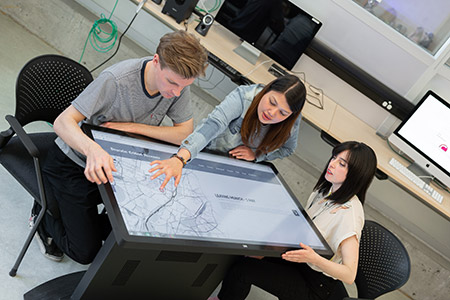 A photo of FCCS professors and students working on touch-screen tablet