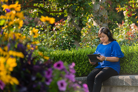 Image of UBC employee sitting in a garden outside using a tablet to access LinkedIn Learning