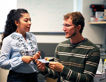 UBCO graduate students Kiana Mirshahidi and Ben Wiltshire demonstrate how small and portable the tiny ice detection senor is. The device has many ramifications, especially for the airline industry.
