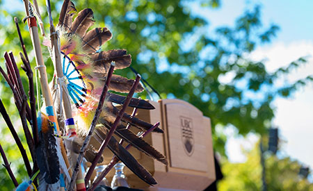 An image of a headdress with eagle feathers, located next to a UBC podium