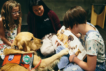 Golden retriever Abby listens while Annie Letheman (right) reads to her sister Ruby and researcher Camille Rousseau (middle) observes.