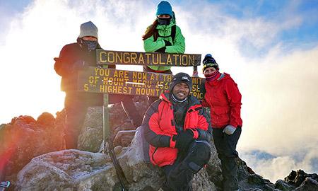 A photo of Willa Holmwood at the summit of Mount Kilimanjaro.