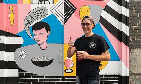 Alumnus Ben Arcega in front of his BNA Brewing mural.
