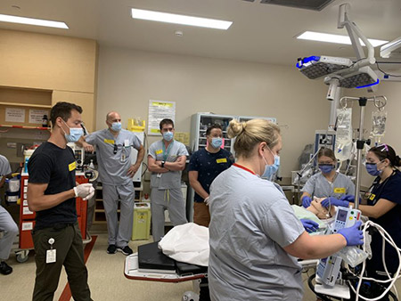 Simulation session in the KGH emergency department. Note: in order to conserve PPE, the team pictured here is wearing PPE appropriate for simulation but not bedside patient care.