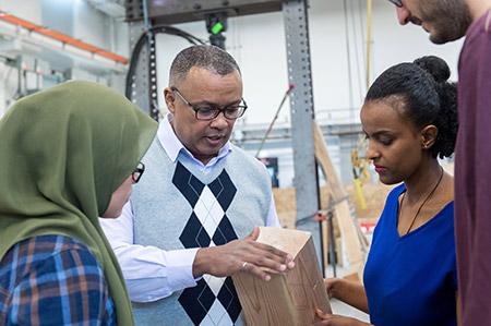 UBCO Engineering Professor Solomon Tesfamariam (centre) examines wood used in mass-timber buildings.